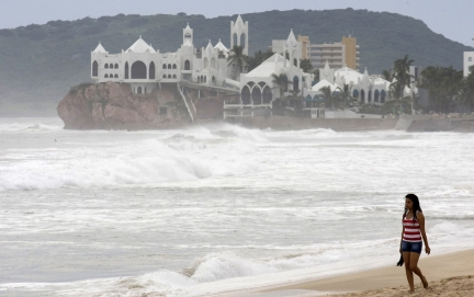 A woman walks on the shore of the beach in Mazatlan on the Mexican mainland and on the Pacific coast near Baja California